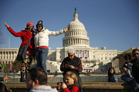 Tourists pose in front of the U.S. Capitol the day before Obama's second inauguration.