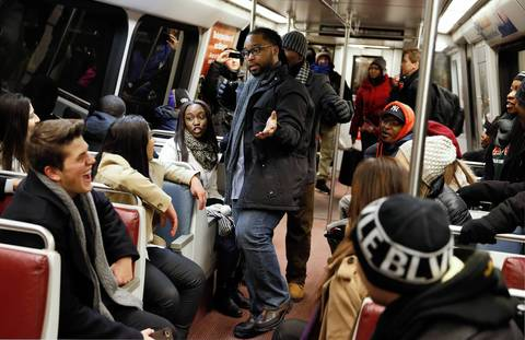 Students from Florida A&M University sing the National Anthem while riding the Metro early Monday morning, in Washington, D.C., as they head to the ceremonial inauguration of President Barack Obama at the U.S. Capitol.