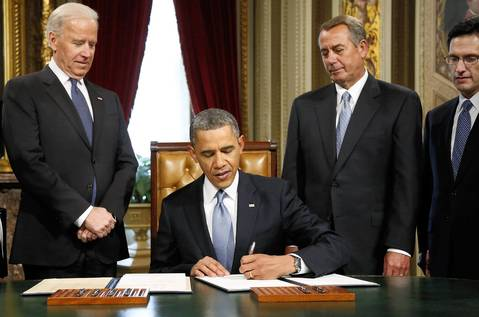 President Barack Obama signs a proclamation to commemorate the inauguration, entitled a National Day of Hope and Resolve, directly after swearing-in ceremonies in the U.S Capitol in Washington. He is flanked by U.S. Vice President Joe Biden, House Speaker John Boehner (R-OH) (second from right) and House Majority Leader Eric Cantor (R-VA), right.