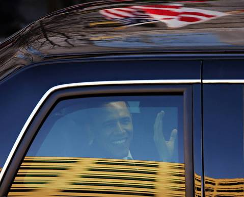 President Barack Obama waves from his car during the inauguration parade along Pennsylvania Avenue in Washington D.C.