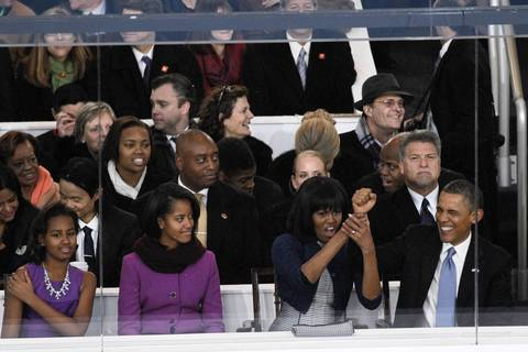 First lady Michelle Obama gives President Barack Obama help cheering as they watch the Inaugural Parade from a viewing stand near the White House in Washington, D.C.