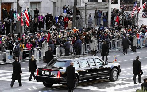 People watch President Barack Obama's limousine pass by during the Inaugural Parade along Pennsylvania Avenue in Washington D.C.