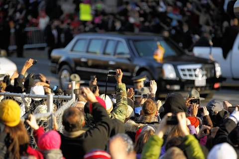People watch the limousine carrying President Barack Obama and first lady Michelle Obama pass during the Inaugural Parade in Washington, D.C.