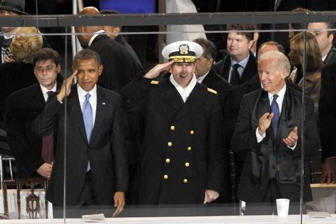 President Obama and Vice President Joe Biden stand with a guest from the U.S. Navy on the reviewing stand during the Inaugural Parade in Washington, D.C.