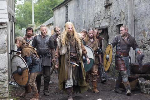 Ragnar, Erik and their crew walk through a conquered village.