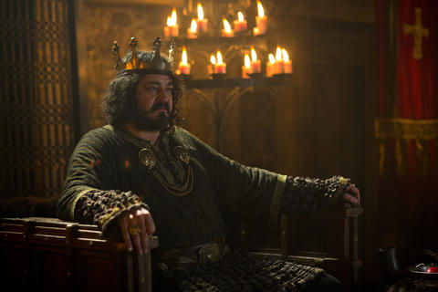 King Aelle (Ivan Kaye), the Saxon King of Northumbria, sits on his throne.