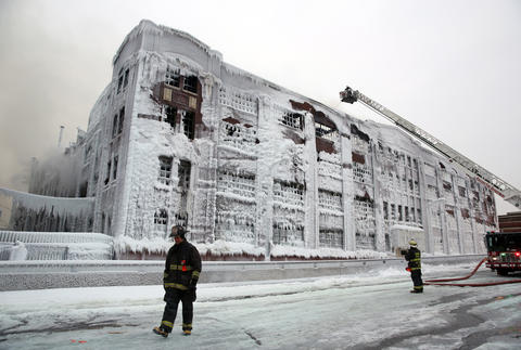 Firefighters spray hot spots on an abandoned warehouse fire on South Ashland Avenue the morning after the fire.