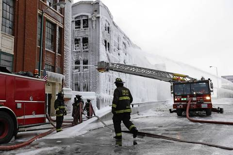 Chicago firefighters attack hot spots at the scene of 5-11 alarm warehouse fire on South Ashland Avenue in Chicago, two days after the fire prompted the largest fire department response in years.
