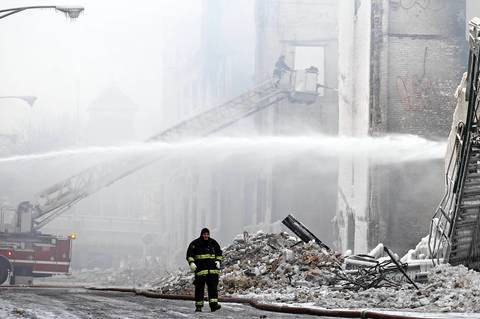 Firefighters hose down hot spots at the scene of 5-11 alarm warehouse fire on South Ashland Avenue in Chicago, two days after the fire prompted the largest fire department response in years.