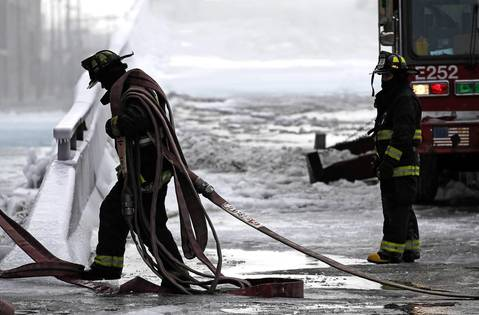 A Chicago firefighter drags equipment to hose down hot spots at the scene of 5-11 alarm warehouse fire on South Ashland Avenue in Chicago, two days after the fire prompted the largest fire department response in years.