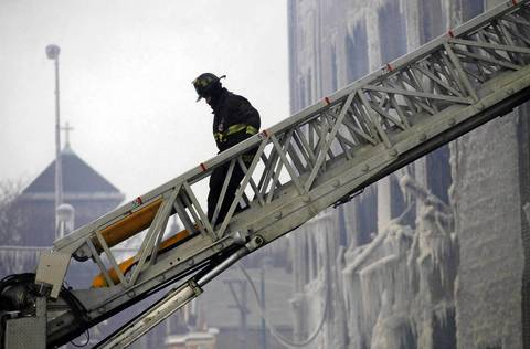 A Chicago firefighter heads down a fire ladder after working to extinguish a rekindled fire at the scene where a 5-11 alarm warehouse fire occurred on South Ashland Avenue in Chicago two days earlier. The fire prompted the largest fire department response in years.