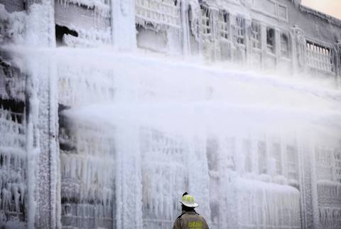 Firefighters pour more water into the Bridgeport neighborhood warehouse as it rekindled on Thursday. Fire officials said they expected the fire to start up again because of the magnitude of Tuesday night's 5-11 alarm fire and the old timber in the warehouse.
