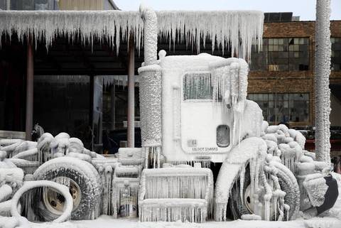 A truck is encased in ice near the Bridgeport warehouse that rekindled two days after it was gutted by a massive extra-alarm blaze.