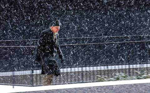 A man braves a sudden snow shower near the Dirksen U.S. Courthouse in Chicago.
