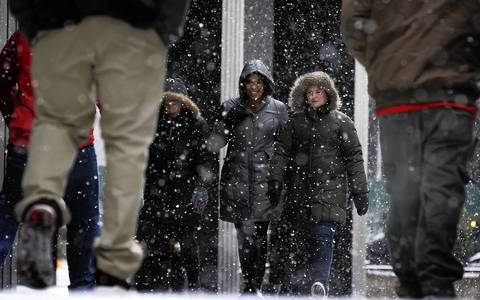 Pedestrians deal with a burst of lake-effect snow storm as they make their way along Michigan Avenue in Chicago.