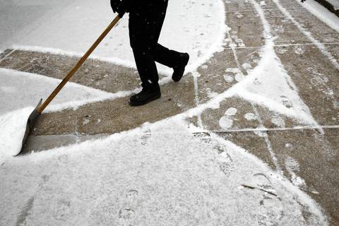 A man shovels snow on Franklin Street near Ontario Street.