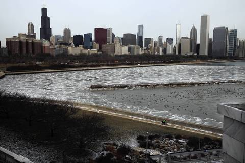 A lone bicyclist rides along the broken ice floes of the lakefront near the Shedd Aquarium in Chicago.