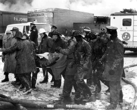 Fire Department Chaplain Monsignor William Gorman, wearing a white helmet, helps with injured firefighters as they are pulled from the rubble of the 1961 Hubbard Street fire. Nine fireman were killed during the Jan. 28, 1961 fire that started in a bakery supplies warehouse.