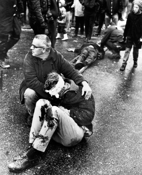 A passerby appeals for help for a victim of the explosion at Mickelberry's Food Products on February 7, 1968, as firemen attempt to help two other victims.