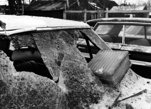 A glass block hurled from the Mickelberry's Food Products building explosion, lies partly through a windshield of one of the cars in a used car lot across the street from the demolished factory. It was debris like this that injured firefighters and people on the street who were in the vicinity of the explosion on Feb. 7, 1968.