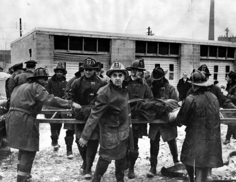 One of the fire department ladders becomes a stretcher for an injured fireman as a squad of his comrades carries him from the explosion at Mickelberry's Food Products plant. A battalion chief, wearing a white helmet, leads the way as the ladder is carried to one of the ambulances at the scene on February 7, 1968.