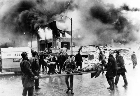 A ladder becomes a stretcher for an explosion victim as flames engulf what remains of the Mickelberry's Food Products building at 801 W. 49th Place on February 7, 1968.