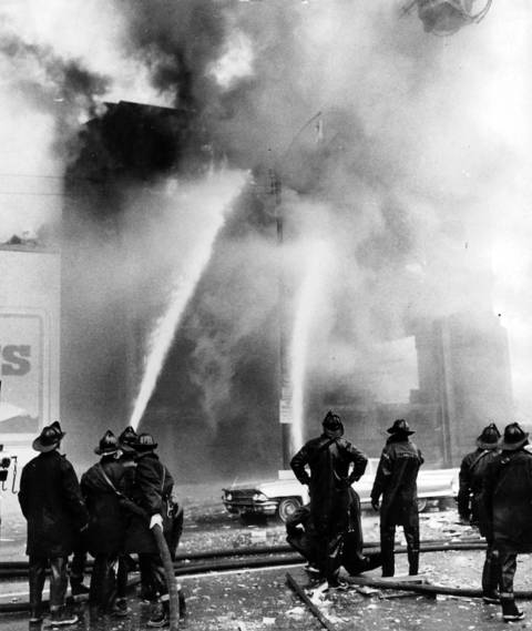 Firemen train their hoses on the blazing Mickelberry's Food Products building on Feb. 7, 1968. The fire and explosions occurred as shifts were changing, killing nine people.
