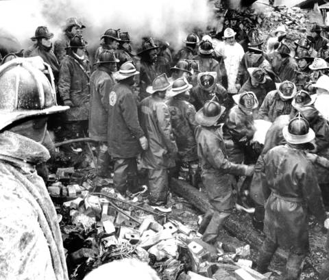 Firemen carry away the body of a fallen comrade after the body was dug out from under bricks at the extra alarm warehouse fire of 1961 at Hubbard and Des Plaines Streets.