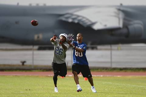 Bears cornerback Tim Jennings intercepts the ball in front of Giants wide receiver Victor Cruz during practice at Joint Base Pearl Harbor-Hickam.