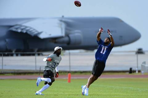 Larry Fitzgerald catches the ball in front of the Bears' Charles Tillman during practice at Joint Base Pearl Harbor-Hickam.