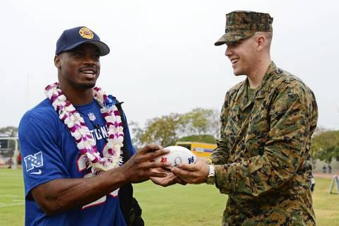 Adrian Peterson autographs a football for Marines member Thaddeus Rix.