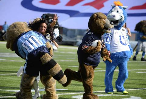 Bears mascot Staley carries the ball as Titans mascot T-Rac blocks Rams cheerleader Michelle Love in a scrimmage.