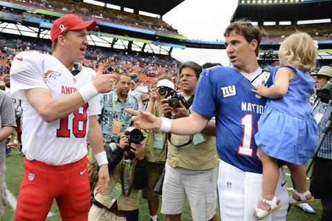 AFC quarterback Peyton Manning shakes hands with NFC quarterback Eli Manning.