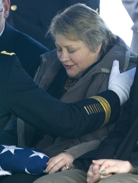 A flag is presented to Julie Chambers following the funeral service for her son, Sgt. David James Chambers, at Clark Cemetery in Hampton on Saturday.