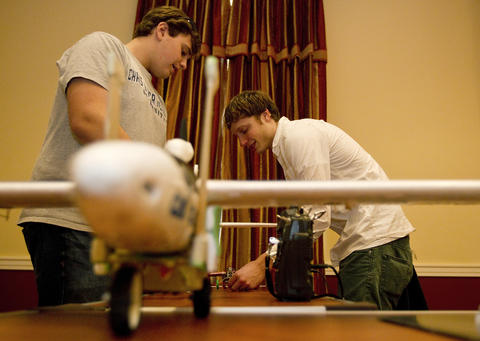 Austin Suhler and Jake Tarren work on a small glider at the Fourth Annual Workshop on Intelligence and National Security at Christopher Newport University on Tuesday. The pair have been working on the project this semester and say they hope the plane will eventually fly autonomously with target acquisition and geotracking.