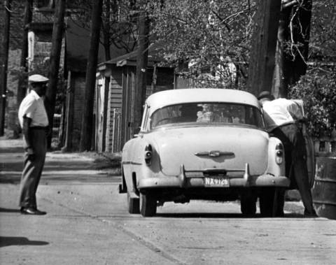The policy runner then opens the car door, reaches into the front seat and picks up a bag containing hundreds of policy slips on May 7, 1964.