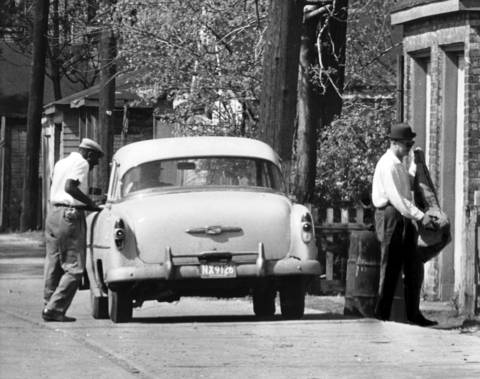 Unaware of the police trap, the policy runner makes his way to a nearby door with a bag containing policy slips on May 7, 1964.