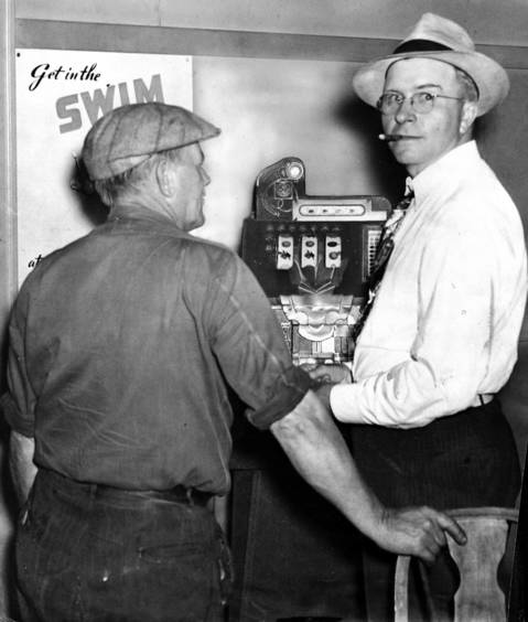 This picture of two men using a slot machine to gamble in a tavern on July 25, 1942 brought threats against Chester Nichols, Chicago Tribune photographer-reporter. Nichols took the picture in Uncle Tom's tavern on Waukegan Road near Northbrook, Ill. Anthony Fragassi of Evanston, who made the threats, was seized by police. The episode gave impetus to State's Attorney Courtney's investigation into syndicate gambling.