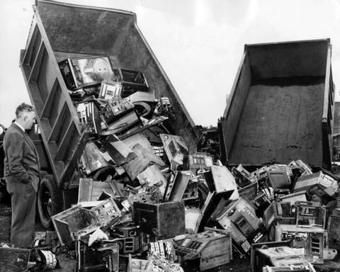 Lieutenant Thomas Kelly of the state's attorney's office stands beside two trucks as they dump 1,000 slot machines into the Bridewell prison stone quarry at 26th and California Avenue on August 21, 1939. The machines were accumulated during raids over the last two years and had been in storage.