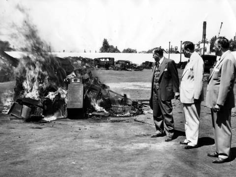 Anthony Ghersovich, left, and Edward Eisner, state's attorney's investigators, and Warden Frank G. Sain, right, watch as 66 slot machines burn at Bridewell (Chicago House of Corrections) junk yard on June 14, 1951.