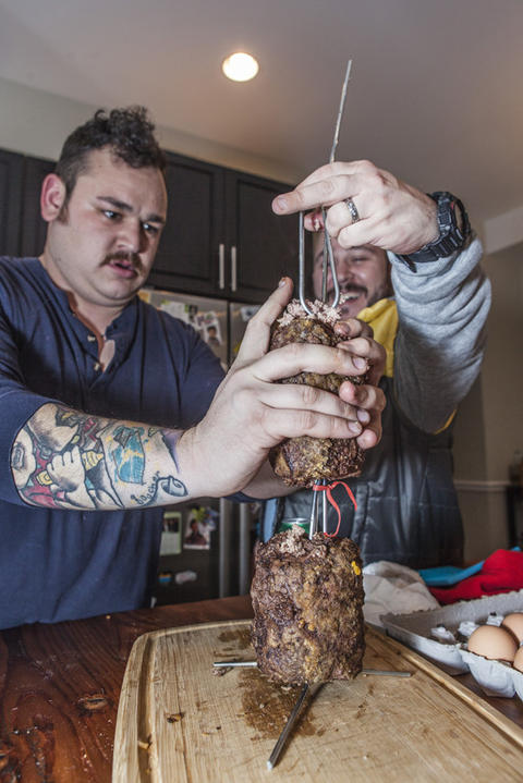 Members of meat enthusiasts group ManBQue work on creating a Vince Lombardi Trophy entirely out of meat.