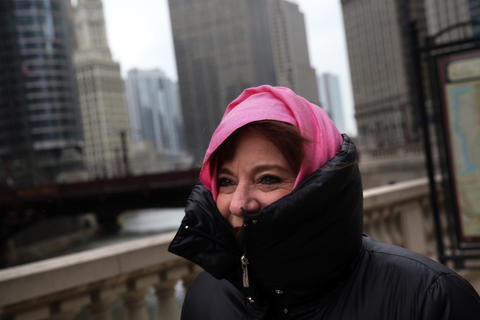 Pat Mendoza walks along Wacker Drive. She is in Chicago for business. Temperatures dropped dramatically into the teens after record-setting warmth earlier in the week.