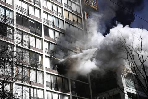A jet of water from a fire hose shoots out of the windows of a condo in a high-rise building in the 200 block of E. Ontario Street in downtown Chicago.