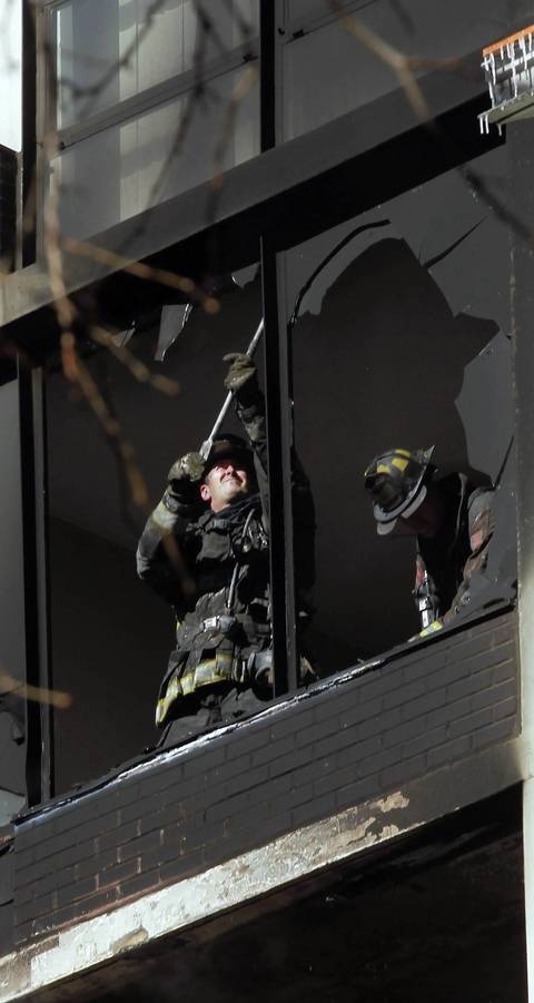 Chicago firefighters remove shards of glass from window framing in a condo that caught fire in the 200 block of E. Ontario Street in downtown Chicago.