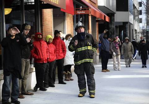 A firefighter and passersby watch from a sidewalk as Chicago firefighters battle a high-rise condo fire in the 200 block of E. Ontario Street.