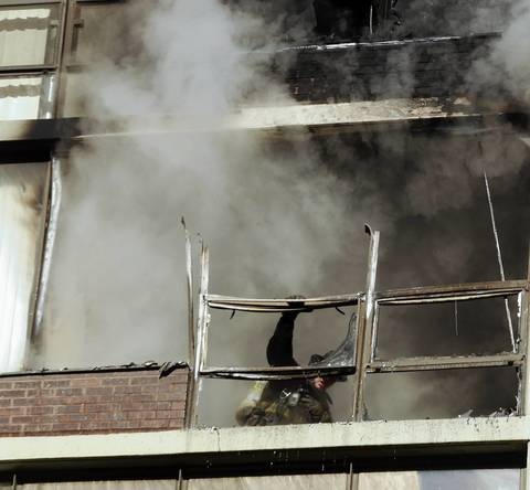A Chicago firefighters grasps what is left of a window framing in condo that caught fire in a high-rise building in the 200 block of E. Ontario Street in downtown Chicago.