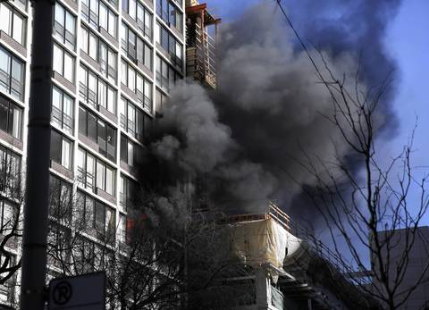 Fire and smoke billow from a high-rise building fire in the 200 block of E. Ontario Street in downtown Chicago.