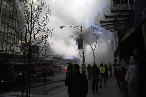 People watch as Chicago firefighters work to extinguish a blaze in a high-rise building in the 200 block of E. Ontario Street in downtown Chicago.