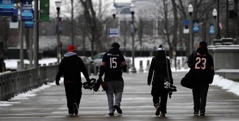 A group walks with their hockey skates to enjoy a day of free skating on the ice rink constructed in Soldier Field.