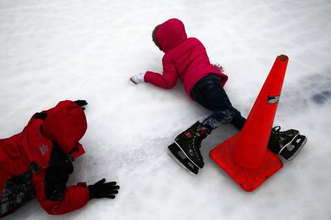 Children fall as they enjoy free ice skating on the Soldier Field ice rink.